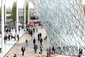 people walking beside sculptural glass structure