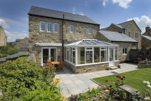 two storey house with conservatory, green grass and blue sky